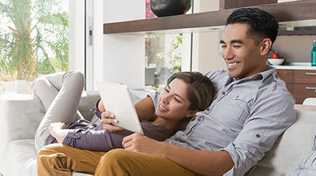 A couple relaxing on a couch while looking at a tablet