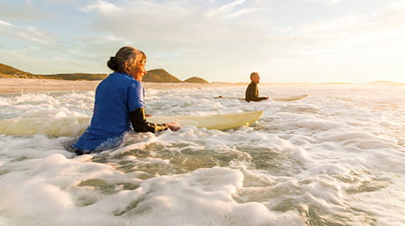 Women and man holding surfboards in the ocean surf