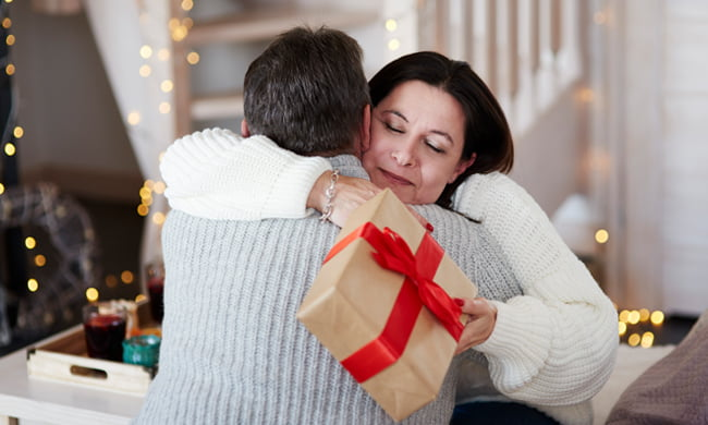 a couple embrace with woman holding gift box